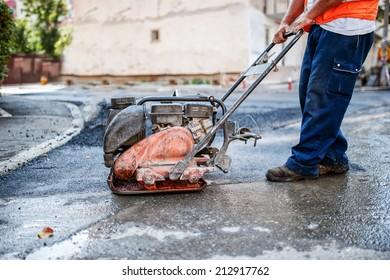 asphalt worker at road repairing with manual compactor plate