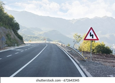 Asphalted mountain road with sharp sharp turn near the cliff. Traffic sign
