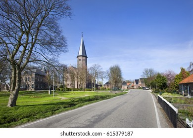 Asphalted road in village Kethel with church Jacobuskerk in the Netherlands