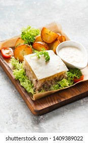 Aspic dish served on wooden plate with roasted potatoes and vegetables with bowl of sauce