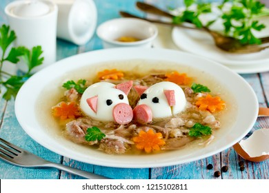 Aspic jellied pork meat holodets decorated with boiled eggs shaped funny pigs, carrot flowers and green parsley, traditional russian dish holodets for festive dinner