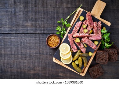 Aspic of a pig prime quality meats from the head and veal shank preserved into a jelly, served with pickles, lemon, parsley, mustard with slices of rye bread, close-up, copy space