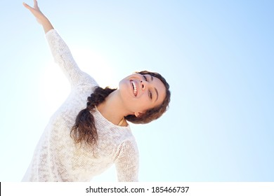 Aspirational energetic portrait of an attractive young woman being playful and enjoying life with her arms stretched against a sunny blue sky with the sun rays filtering in. Joyful lifestyle.