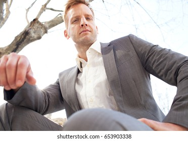 Aspirational portrait of powerful slick and attractive businessman sitting against a sunny sky in the city, looking at camera, confident and strong. Professional leader wearing smart suit, outdoors.