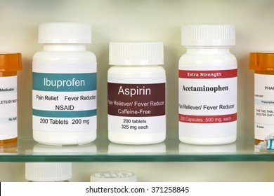 Aspirin, ibuprofen, and acetaminophen in medicine cabinet. Labels are created by the photographer.
