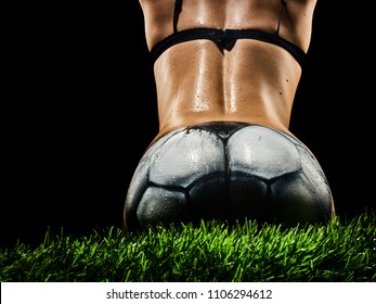the ass of a naked girl with a beautiful waist, painted in a soccer ball, sits on the green grass. Beautiful body art on the theme of football on a black background