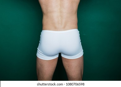 ass young guy in white underwear. inflated buttocks on colored paper background