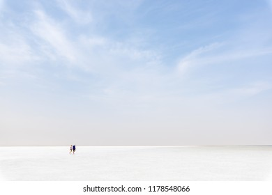 ASSALE LAKE, ETHIOPIA -- AUGUST 17, 2018: unidentified couple walks on the salty surface of lake Assale. This  lake is one of the saltiest of the world.