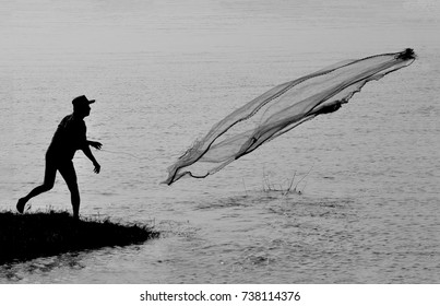 ASSAM, INDIA:- A fisherman throwing his fishing net to mighty Brahmaputra river somewhere near in Nimati.  It reflects the fishing profession, the livelihood of many Assamese.