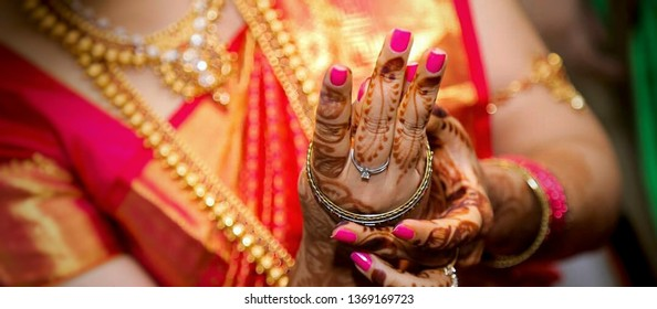 An assamese bride trying to wear a bangle in her wedding day