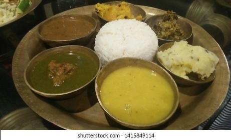 Assamese cuisine - Vegetarian thali consisting of plain rice, yellow dal, green herb curry, black dal, pumpkin sabji, banana flower stir fry, mashed potato called aloo pitika. Location Assam India.