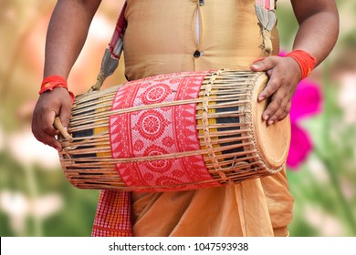 Assamese musician playing traditional musical instrument.