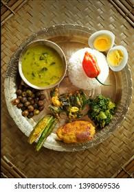 Assamese Thali. Assamese food serving on bell metal plate and bowl.