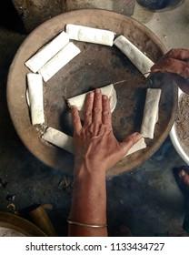 An Assamese women preparing Assamese traditional cake Bora Pitha