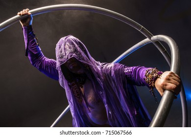 Assassin. Fairy-tale character in a bright purple suit with a hood and an extraordinary weapon.