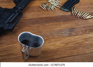 assault rifle and cup of coffee on wooden table background