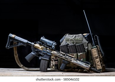 Assault rifle with sight,bulletproof vest,ammo and radio on dark background/Helmet,rifle and military flak jacket