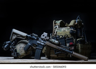 Assault rifle with silencer, bulletproof vest, helmet with night vision device on dark background/Rifle with silencer, bulletproof vest, helmet