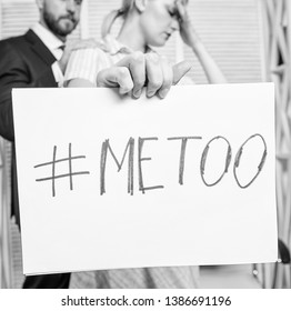 Assault targeted at employee. Girl hold poster hashtag me too while colleague calm down her. Share assault story. Discrimination assault complaint. Scandal sexual abuse victim. Assault at workplace.
