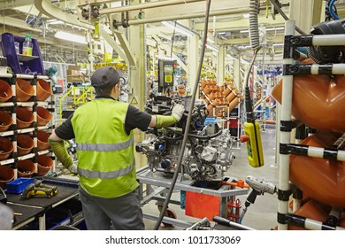 Assembling engines in an automobile factory. Production worker