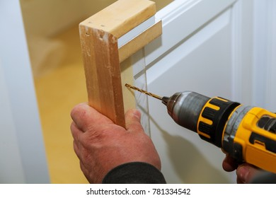 Assembling furniture and drills the cabinet door using screwdriver