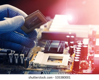 Assembling high performance personal computer, inserting CPU, processor into the motherboard socket, opened PC case in background, shallow depth of field, focus on hand. Studio high-resolution image.
