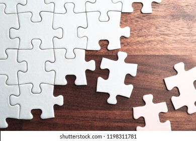 Assembling jigsaw puzzle pieces. Abstract background.Unfinished white jigsaw puzzle pieces on wood table.