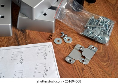 Assembling parts of sofa on brown wooden floor with paper instruction