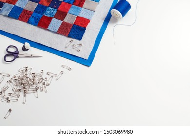 Assembling of a quilt sandwich, curved basting pins and sewing accessories, space for text