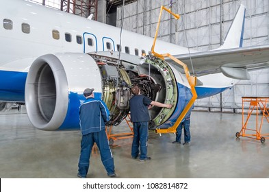 Assembling, replacing engine parts of the plane after repair. Specialist mechanic controls the crane of an airplane. Concept maintenance of aircraft