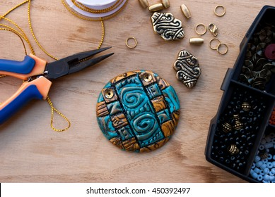 Assembly of jewelry of polymer clay in egypt style with gold elements and box with small beads. Hobby, handicraft. Pilers with unfinished necklace.