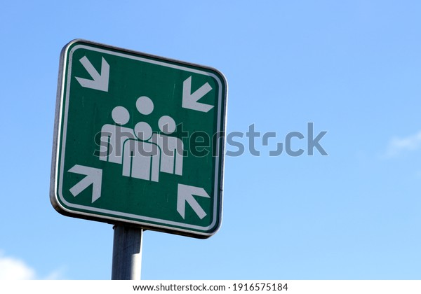 Assembly point, green sign, sky background