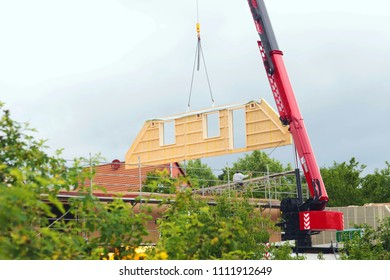 assembly of a prefabricated timber house, crane lifting a gable component in the air