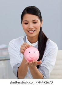 Asserive businesswoman saving money in a piggybank in the office