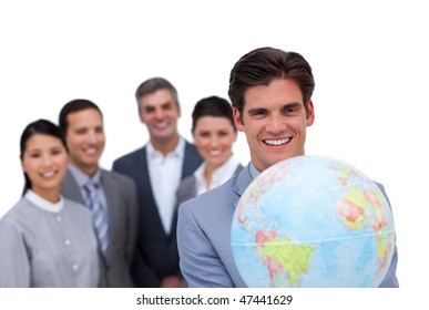 Assertive businessman holding a globe in front of his team against a white background