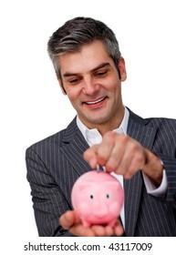 Assertive Businessman saving money in a piggybank against a white background