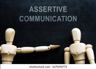 Assertive communication phrase and two wooden figures.