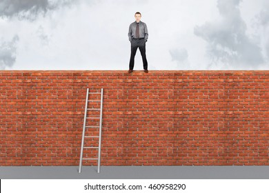 Assertive man stands on the top of a brick wall. Overcoming barriers