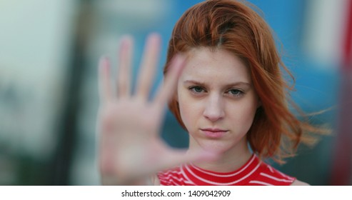 Assertive woman making stop gesture. Strong redhead lady showing hold sign