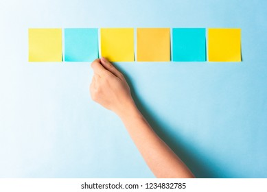 Assessment analysis evaluation concept. Hand choosing multi colored notes on blue background.