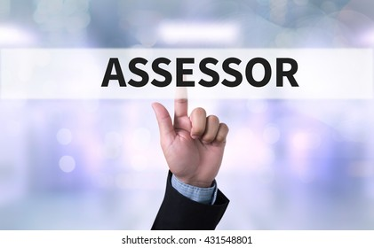 ASSESSOR Business man with hand pressing a button on blurred abstract background
