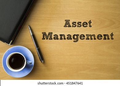 Asset management words writing on wooden desk with notebook, pen and cup of coffee, Business conceptual.