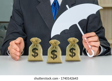 Asset / wealth protection for high net worth individuals, financial concept : Investor holds an umbrella protects dollar bags, depicting a plan to avoid risk and protect asset or business from claims