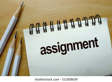 assignment text written on a notebook with pencils