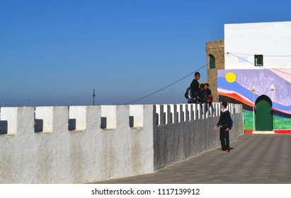 ASSILAH, MOROCCO - NOVEMBER 10, 2015: Moroccan school children playing on the city walls of Assilah