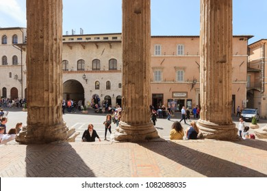 Assisi, Italy - April 08, 2018: Temple of Minerva in Piazza del Comune with tourists