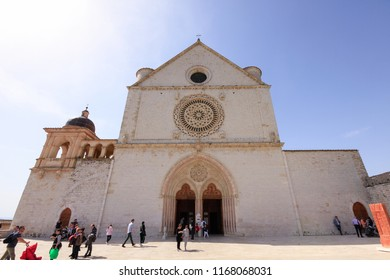 Assisi, Italy - April 08, 2018: The facade of the Basilica of Saint Francis of Assisi with tourists in a sunny day