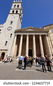 Assisi, Italy - April 08, 2018: The Temple of Minerva and tourists, the temple is an ancient Roman building, currently it houses a catholic church, Santa Maria sopra Minerva, built in 1539