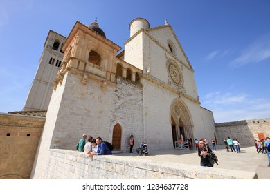 Assisi, Italy - April 08, 2018: The facade of the Basilica of Saint Francis of Assisi with tourists in a sunny day on the parvis