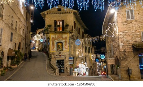 ASSISI, ITALY - DECEMBER 21, 2018: Medieval street of Assisi with christmas decorations at winter night, Umbria